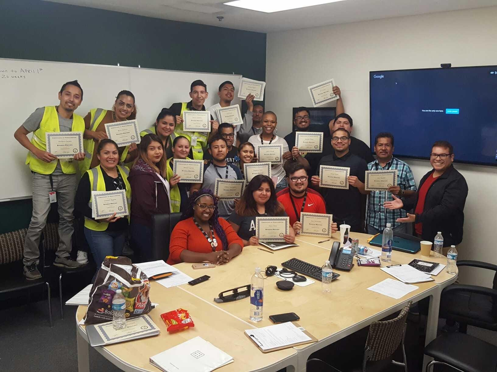 A group of employees at Black Tux with Leadership completion certificates
