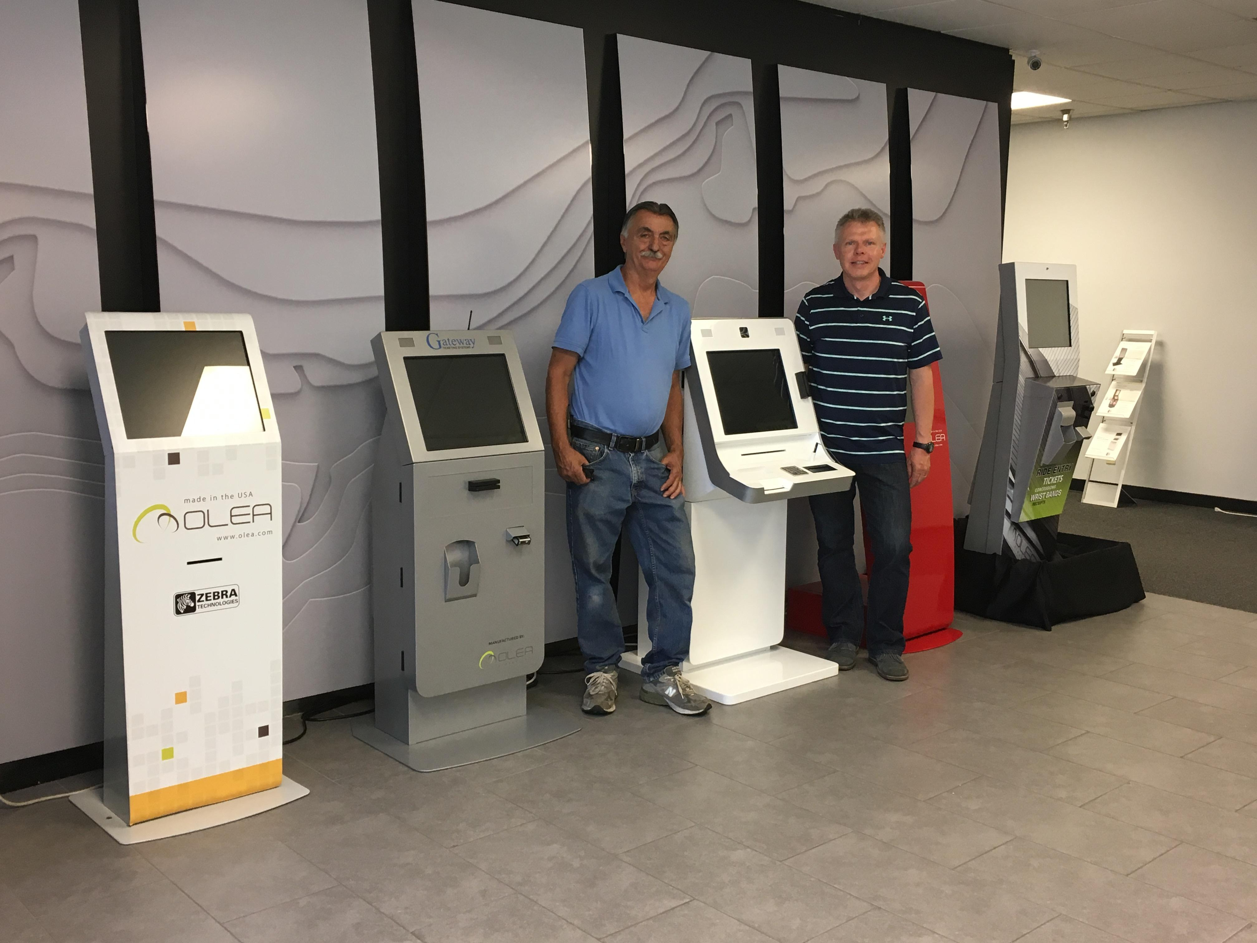 Two men standing by a kiosk machine at Olea company
