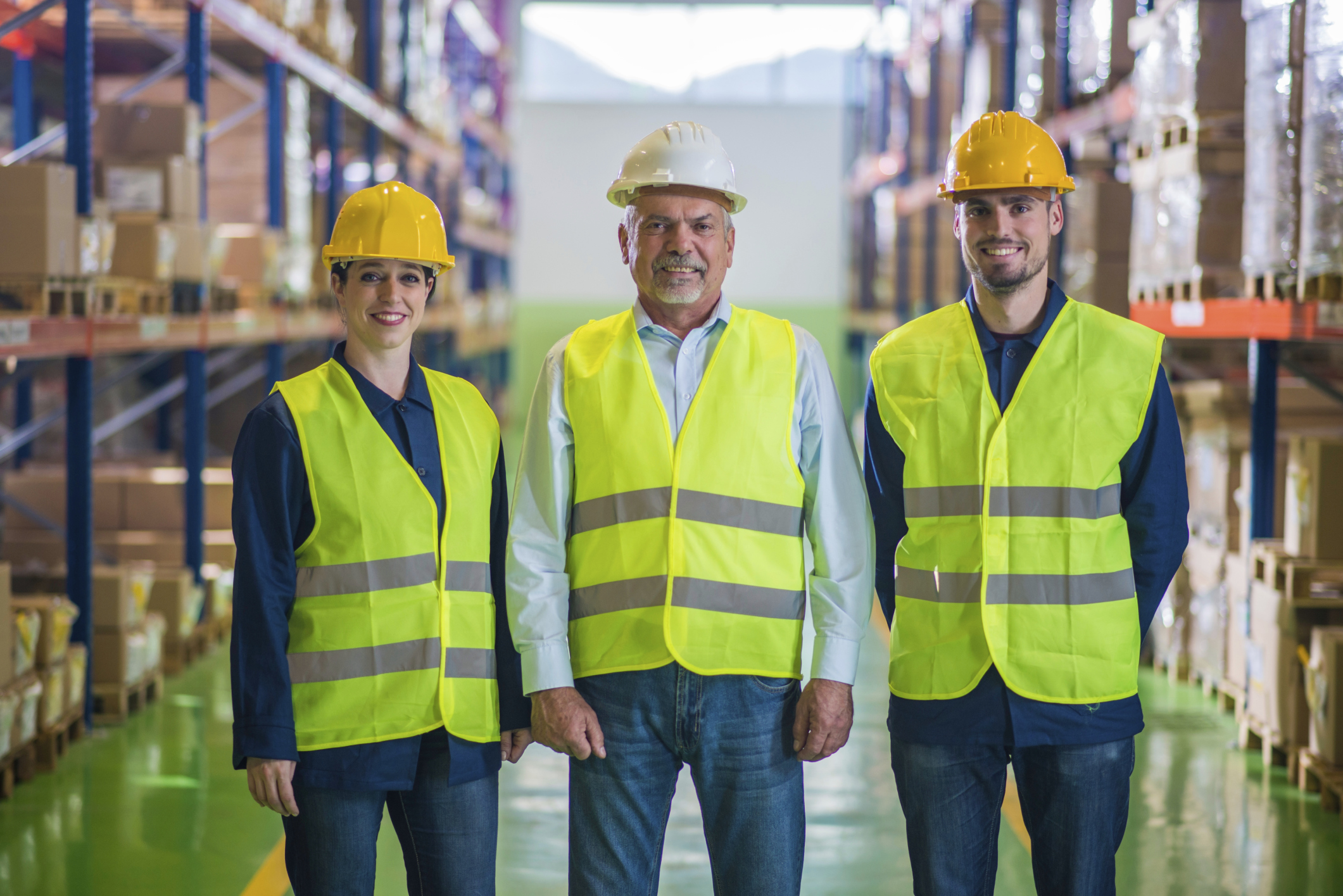 Two men and a woman in safety hard hats and vests working in a warehouse