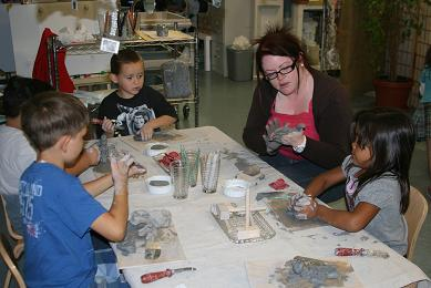 Diana working with 3 young children and clay