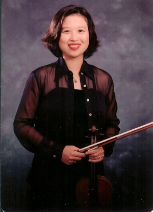 Tammy Tsai standing holding her violin.