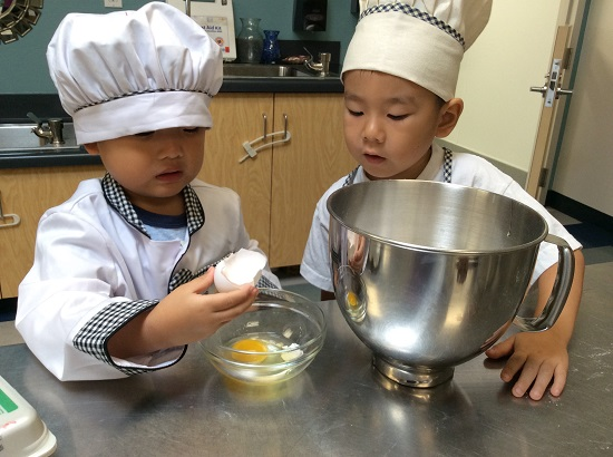 Boy and girl cracking an egg to bake