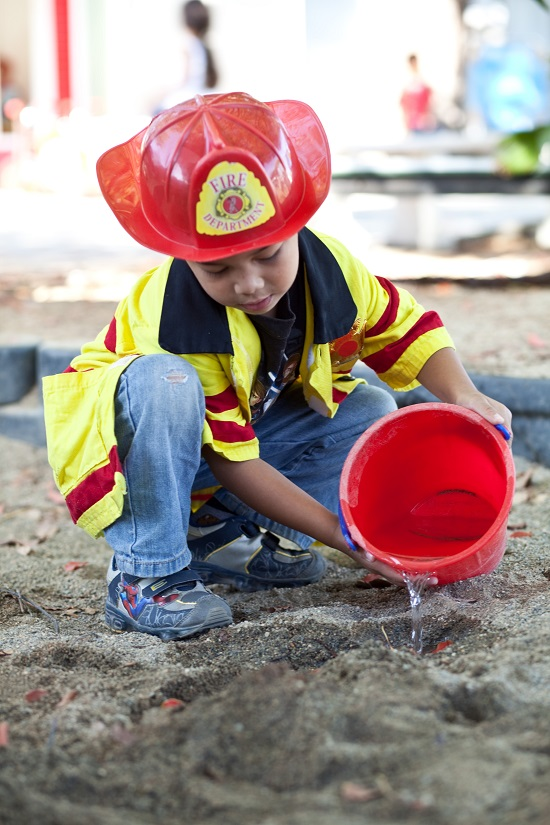 Little boy dressed as a firefighter making mud