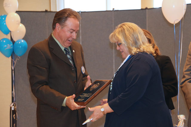 Stephen Richardson presents employee of the year plaque to Janice Cole.