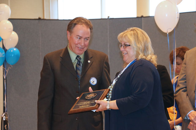 Stephen Richardson looks on as Janice Cole receives her employee of the year plaque.