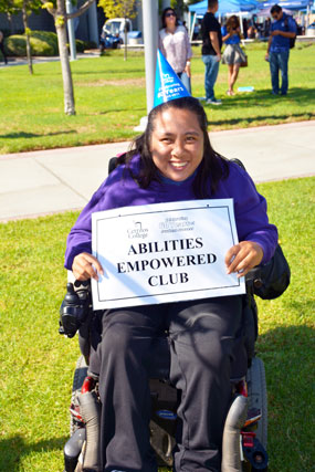 Individual in a wheelchair with a sign, Abilities Empowered Club